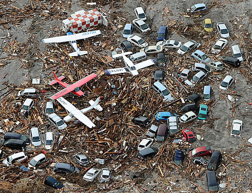 Light planes and vehicles sit among the debris after they were swept by a tsunami that struck Sendai airport in northern Japan on March 11, 2011. A magnitude 8.9 earthquake slammed Japan's eastern coast Friday, unleashing a 13-foot (4-meter) tsunami that swept boats, cars, buildings and tons of debris miles inland. (Associated Press/Kyodo News)