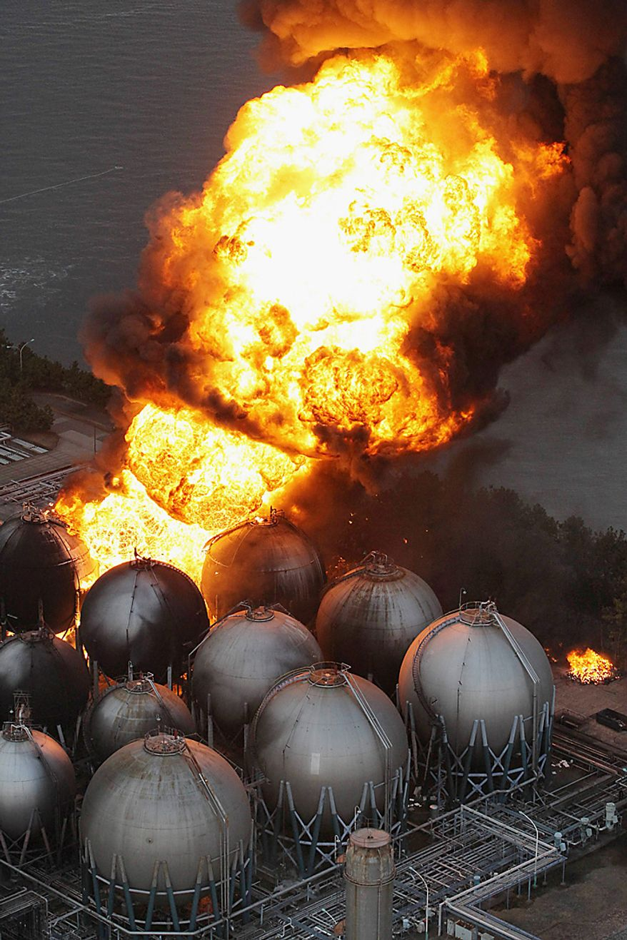 Giant fireballs rise from a burning oil refinery in Ichihara, Chiba Prefecture (state) after Japan was struck by a strong earthquake off its northeastern coast Friday, March 11, 2011. (AP Photo/Kyodo News)