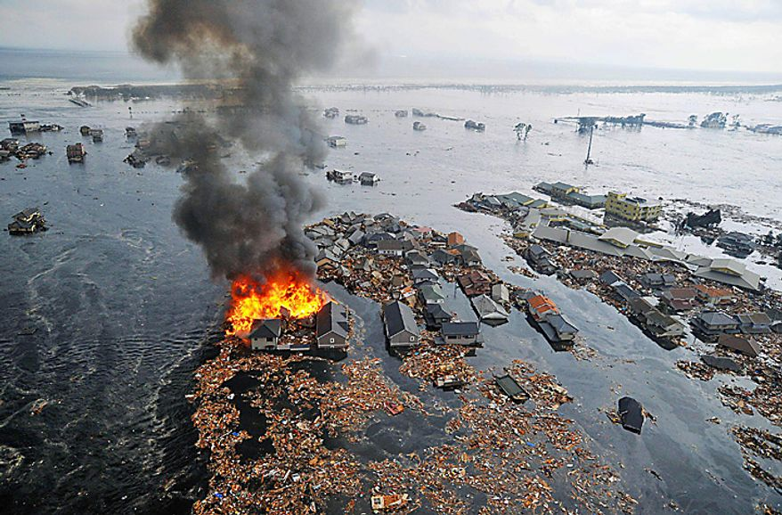 Houses swallowed by tsunami waves burn in Sendai, Miyagi Prefecture (state) after Japan was struck by a strong earthquake off its northeastern coast Friday, March 11, 2011. (AP Photo/Kyodo News)