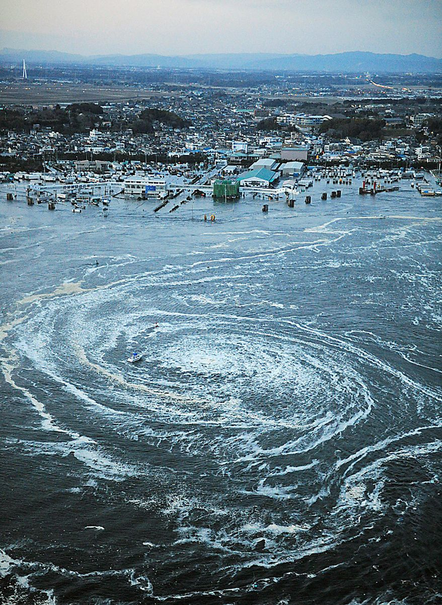 Tsunami waves swirl near a port in Oarai, Ibaraki Prefecture (state) after Japan was struck by a strong earthquake off its northeastern coast Friday, March 11, 2011. (AP Photo/Kyodo News)
