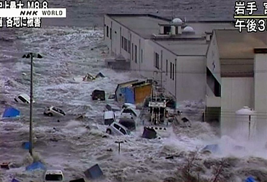 In this video image taken from Japan's NHK TV, a tsunami surge sweeps cars, boats and other debris against a building in Miyaku City, Iwate Prefecture  Japan Friday March 11, 2011 following a massive earth quake. A magnitude 8.9 earthquake slammed Japan's northeastern coast Friday, unleashing a 13-foot (4-meter) tsunami that swept boats, cars, buildings and tons of debris miles inland. Fires triggered by the quake burned out of control up and down the coast.  (AP PHOTO/NHK TV)