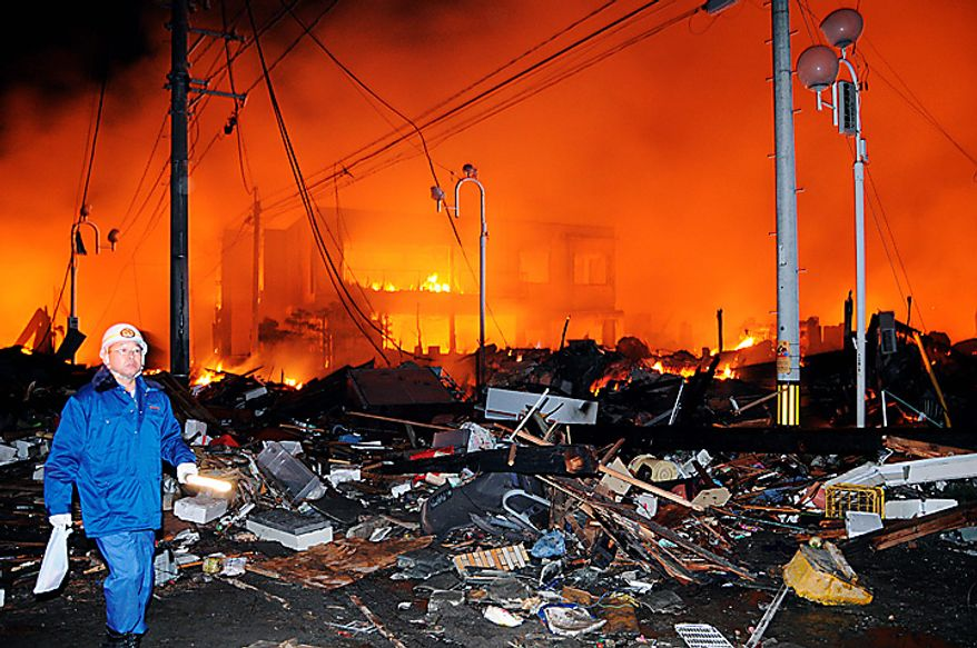 A helmeted man walks past the rubbles and a burning building after a powerful earthquake, the largest in Japan's recorded history, slammed the eastern coasts in Iwaki city, Fukushima prefecture, Japan, Friday, March 11, 2011. (AP Photo/Kyodo News)