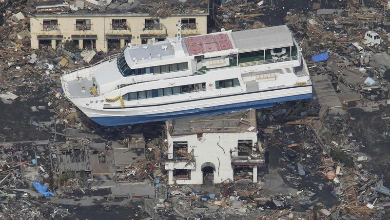 A ferry is stranded atop a building in Otsuchi in Iwate prefecture on Sunday. The Japanese government doubled the number of troops pressed into rescue operations to about 100,000, following the worst-ever earthquake to hit Japan. (Yomiuri Shimbun via Associated Press)