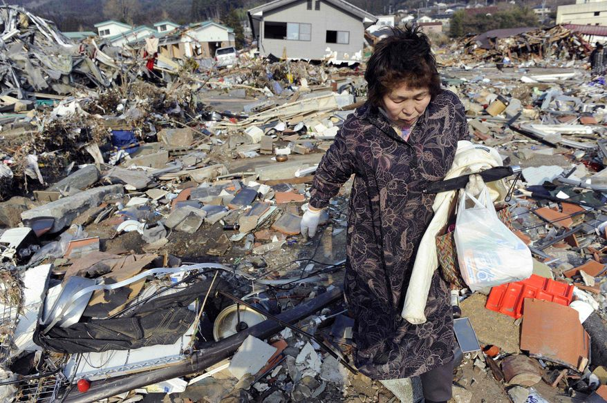 A woman searches through the rubble of her home in Ofunato in Iwate prefecture Sunday. Her house was destroyed in Friday's powerful earthquake-triggered tsunami. At least 1.4 million households were without water Sunday, and 2 million households had no electricity. (Kyodo News via Associated Press)