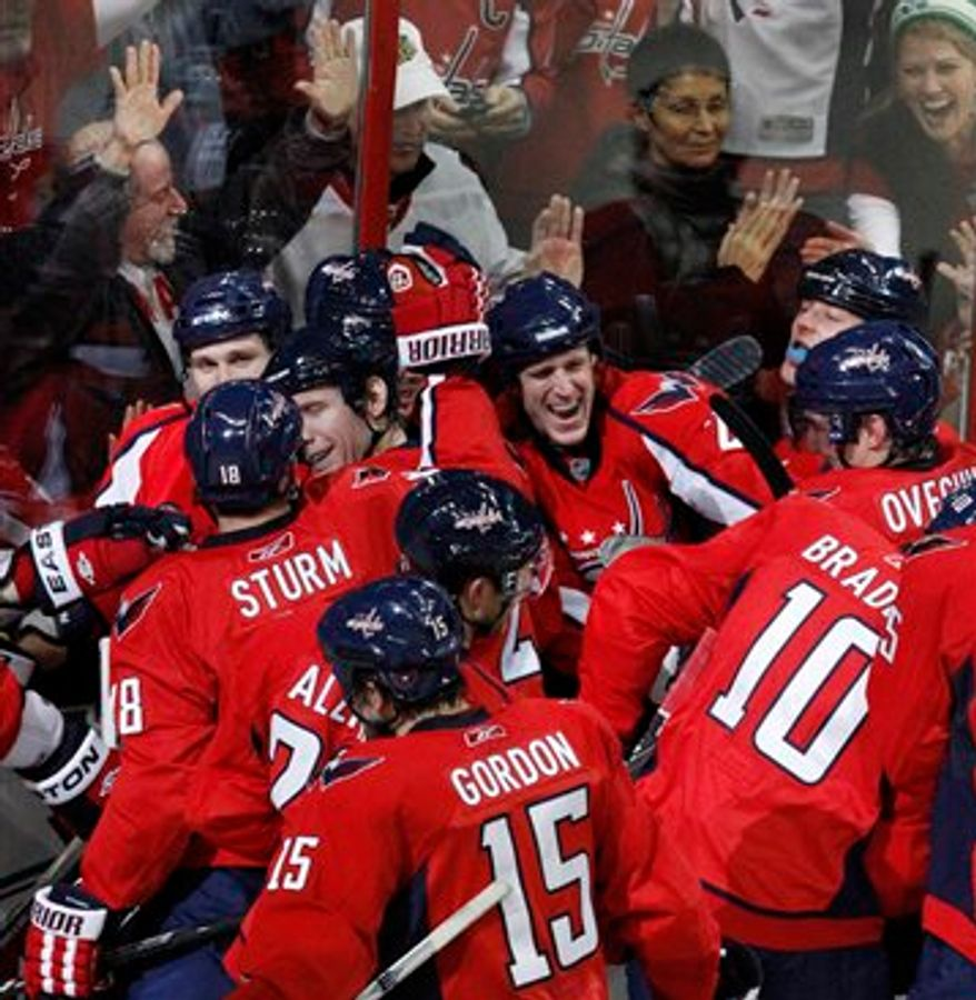 The Washington Capitals celebrates on the ice as fans cheer against the glass after the Capitals won during overtime against the Chicago Blackhawks in an NHL hockey game at the Verizon Center in Washington, on Sunday, March 13, 2011. The Capitals won 4-3. (AP Photo/Jacquelyn Martin)