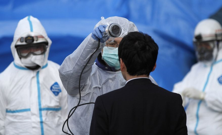 An official scans a man for radiation at an emergency center in Koriyama, Japan, on Sunday, March 13, 2011, two days after a giant earthquake and tsunami struck the country's northeastern coast. (AP Photo/Gregory Bull)