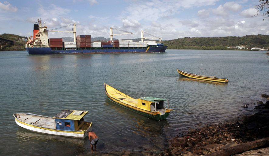 """A cargo ship heading for the Panama Canal passes fishing vessels. Colombia's president dreams of creating a rail line that would capture some of the trade now using the Canal. Colombia's President Juan Manuel Santos, below, says the plan for a railway linking the Caribbean Sea and Pacific Ocean is """"quite advanced"""" but others doubt it. (Associated Press)"""