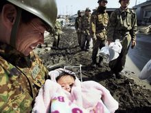 SURVIVOR: A 4-month-old girl was found alive in Ishinomaki on Monday. The baby's parents, who were holed up in their home for three days, had handed the child to soldiers. (Yomiuri Shimbun via Associated Press)