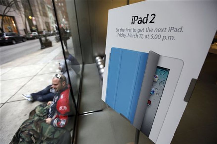 FILE - In this March 9, 2011 file photo, an Associated Press reporter demonstrates the Garage Band application on the Apple iPad 2 in San Francisco. Apple Inc.'s updated version of its iPad tablet computer will be available in stores Friday afternoon but those who can't wait to say they own the gadget can beat the crowds by ordering one online before the sun rises.(AP Photo/Jeff Chiu, file)