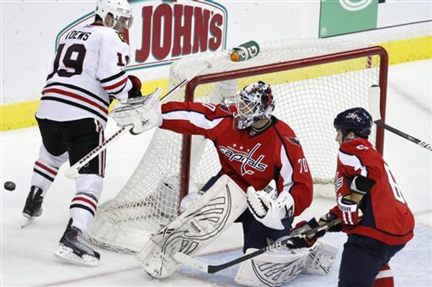 Chicago Blackhawks defenseman Nick Leddy (8) and Washington Capitals defenseman Scott Hannan (23) try to  control the puck during the second period of an NHL hockey game at the Verizon Center in Washington on Sunday, March 13, 2011.  (AP Photo/Jacquelyn Martin)