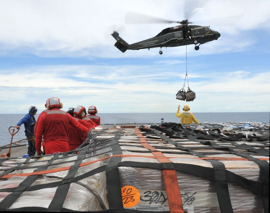 Sailors aboard the U.S. 7th Fleet command ship USS Blue Ridge (LCC 19) in the South China Sea stand by to move pallets of humanitarian relief supplies across the ship's flight deck to replenish the USNS Rappahannock. The Blue Ridge is ensuring the crew of the Rappahannock is ready if directed to assist with earthquake and tsunami relief operations in Japan. (AP Photo/U.S. Navy, Mass Communication Spec. 3rd Class Fidel C. Hart)