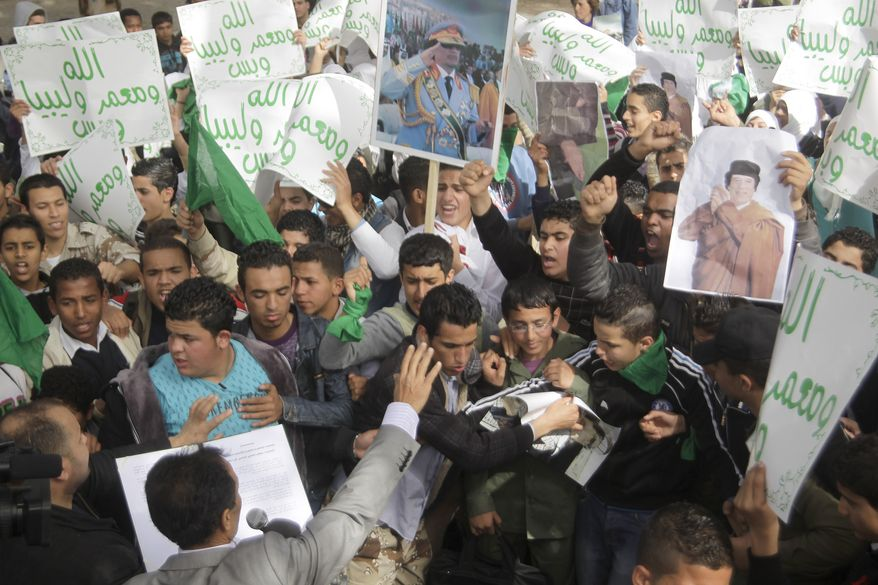 """Libyan students shout slogans during a pro-Gadhafi rally in the parking lot of the Rixos Hotel, where the foreign press is staying, in Tripoli, Libya, on Monday, March 14, 2011. Teachers brought the students from neighborhood schools to demonstrate. The signs read, """"God, Moammar and Libya."""" (AP Photo/Jerome Delay)"""