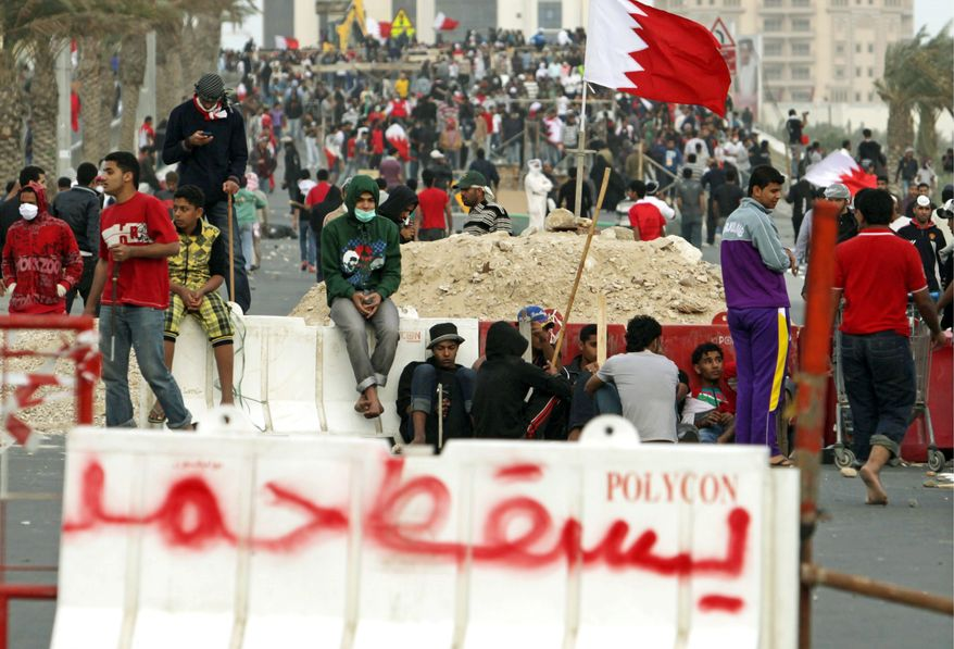 Bahraini anti-government protesters wait at barriers they set up for Saudi forces in Manama, Bahrain. A Saudi-led military force crossed into Bahrain to prop up the monarchy against widening Shiite demonstrations. (Associated Press)