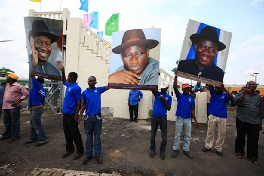 Nigeria President Goodluck Jonathan, Centre, waves to the crowd as he arrived for a ceremony to commission new locomotive trains, in Lagos, Nigeria, Saturday, March 12, 2011. (AP Photo/Sunday Alamba)
