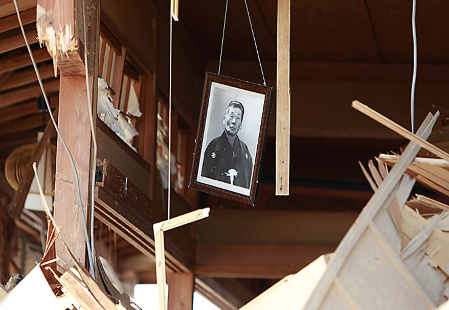 A photo hangs from the remains of a house in the seaside town of Toyoma in northern Japan on Monday, March 14, 2011, three days after a giant quake and tsunami struck the country's northeastern coast. (AP Photo/Mark Baker)