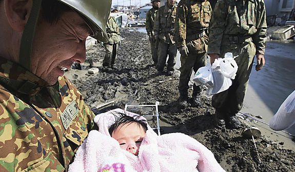 A Japan Self-Defense Force member reacts after rescuing a 4-month-old baby girl in Ishinomaki, Japan, on Monday, March 14, 2011, three days after a powerful earthquake-triggered tsunami hit the country's east coast. (AP Photo/The Yomiuri Shimbun, Hiroto Sekiguchi)