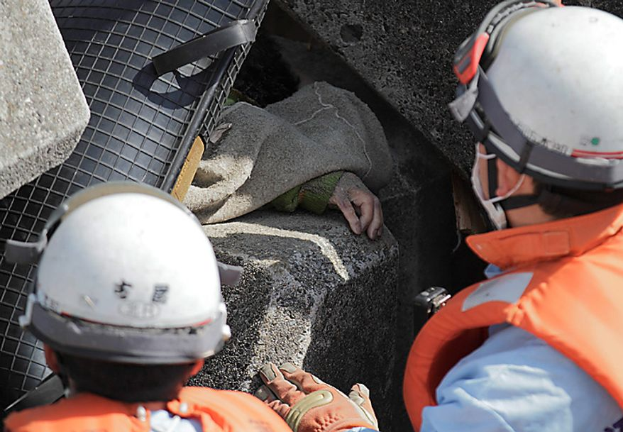 Japanese emergency crews work to free a body pinned among concrete sea barriers on Monday, March 14, 2011, in Toyoma, Japan, three days after a giant quake and tsunami struck the country's northeastern coast. (AP Photo/Gregory Bull)