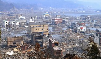 Houses and infrastructure devastated by a strong earthquake and tsunami are seen in Otsuchi, in Japan's Iwate Prefecture, on Monday, March 14, 2011, three days after northeastern coastal towns were devastated by the earthquake and tsunami. (AP Photo/Kyodo News)