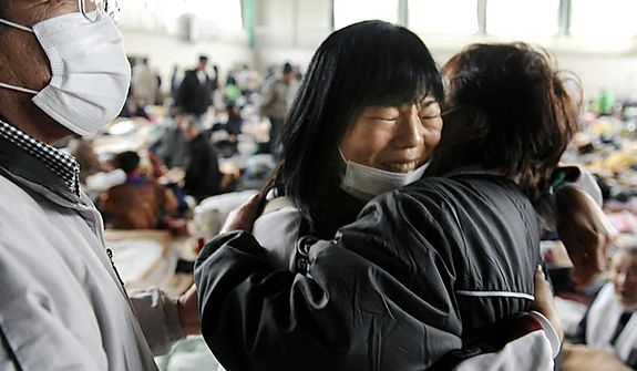 Relatives react as they reunite at a shelter in Kesennuma in Japan's Miyagi Prefecture on Monday March 14, 2011, three days after northeastern coastal towns were devastated by an earthquake and tsunami. (AP Photo/Kyodo News)