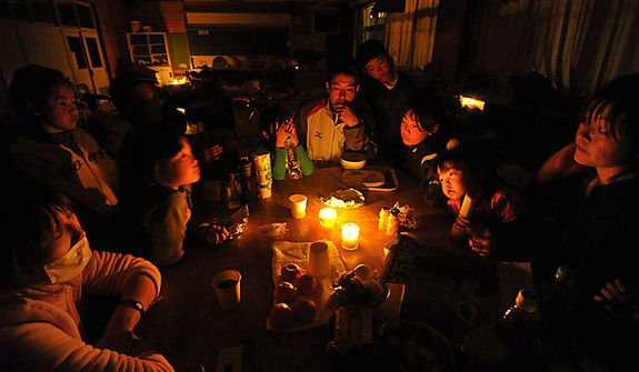 Evacuees gather around the candlelight at a blacked-out shelter on Monday, March 14, 2011, in Yamamoto, Miyagi Prefecture, Japan, on Monday, March 14, 2011, three days after northeastern coastal towns were devastated by an earthquake and tsunami. (AP Photo/Kyodo News)