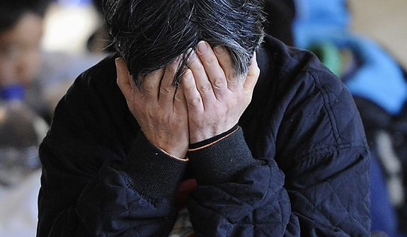 A female evacuee covers her face at a shelter in a temple on Monday, March 14, 2011, in Higashimatsushima, Miyagi Prefecture, Japan, on Monday, March 14, 2011, three days after northeastern coastal towns were devastated by an earthquake and tsunami. (AP Photo/Kyodo News)