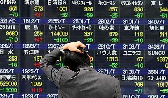 A man reacts while looking at a stock price board in Tokyo on Monday, March 14, 2011, as the Tokyo stock market plunged on its first business day after an earthquake and tsunami of epic proportions laid waste to cities along Japan's northeast coast. Only stock prices of construction and housing business showed upward trend (in red digits). (AP Photo/Eugene Hoshiko)