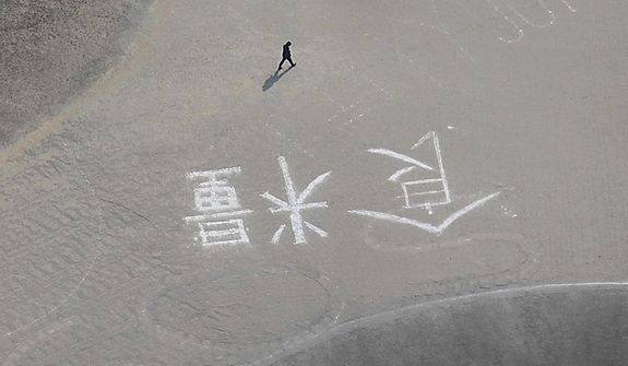 """In this March 13, 2011, photo, a man walks by the Japanese word meaning """"food"""" drawn over fading sign of SOS marked on the ground in Rikuzentakata in Japan's Iwate Prefecture on Monday, three days after a powerful earthquake and tsunami that hit the country's northeast coast. (AP Photo/The Yomiuri Shimbun, Motoki Nakashima)"""