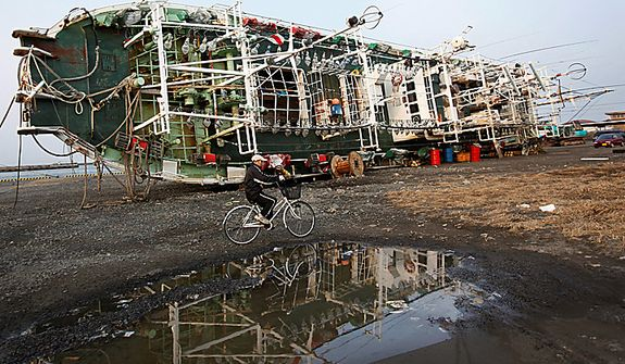 A man bicycles by a beached ship at Hachinohe, Aomori Prefecture, northern Japan, on Monday, March 14, 2011, three days after a powerful earthquake-triggered tsunami hit Japan's east coast. (AP Photo/Shizuo Kambayashi)