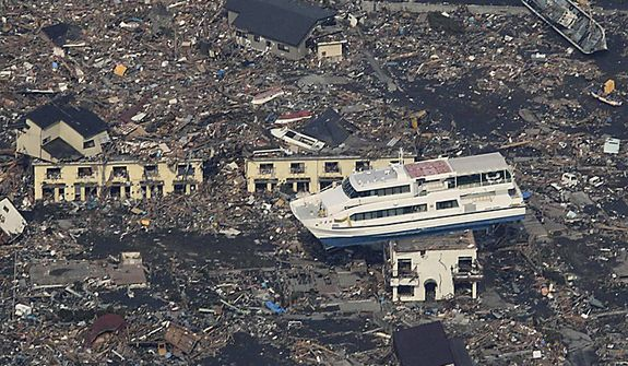 A ferry is stranded atop a building in Otsuchi, Iwate Prefecture, in northern Japan on Sunday, March 13, 2011, two days after a powerful earthquake-triggered tsunami hit the country's east coast. (AP Photo/The Yomiuri Shimbun)