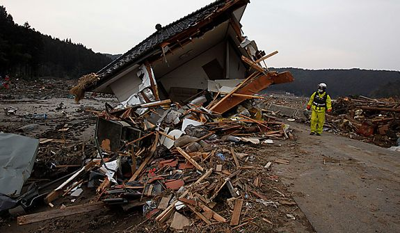 A firefighter examines the damage of a house in Saito, in Japan's Miyagi Prefecture, on Monday, March 14, 2011, after Japan's biggest recorded earthquake slammed the country's eastern coast Friday. (AP Photo/Shuji Kajiyama)