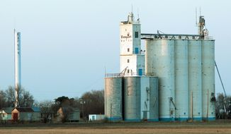 A grain elevator and water tower are seen from an unsurfaced road into Freeport, Kan., a town of just five people. (Associated Press)