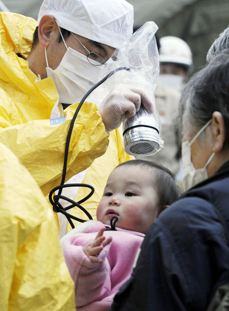 BABY MONITOR: A baby is checked for radiation exposure on Tuesday in Nihonmatsu, a city in Fukushima, where another explosion and a fire at a nuclear-power plant sent radiation levels above normal. (Kyodo News via Associated Press)