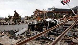 Japan Self-Defense Force members search for survivors of the earthquake and tsunami Tuesday in the devastated city of Ofunato, Japan. (Associated Press)