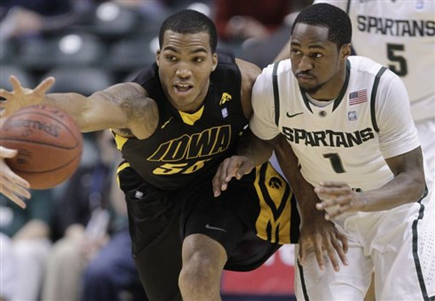 Iowa forward Jarryd Cole (50) and Michigan State guard Kalin Lucas (1) chase a loose ball in the first half of an NCAA college basketball game at the Big Ten Conference tournament in Indianapolis, Thursday, March 10, 2011.  (AP Photo/Michael Conroy)