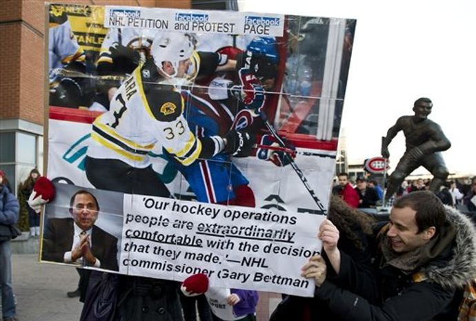 Demonstrators hold up a placard during a protest against violence in hockey and demanding tougher sanctions from the NHL against hits to the head, Tuesday, March 15, 2011, in Montreal. (AP Photo/The Canadian Press, Paul Chiasson)