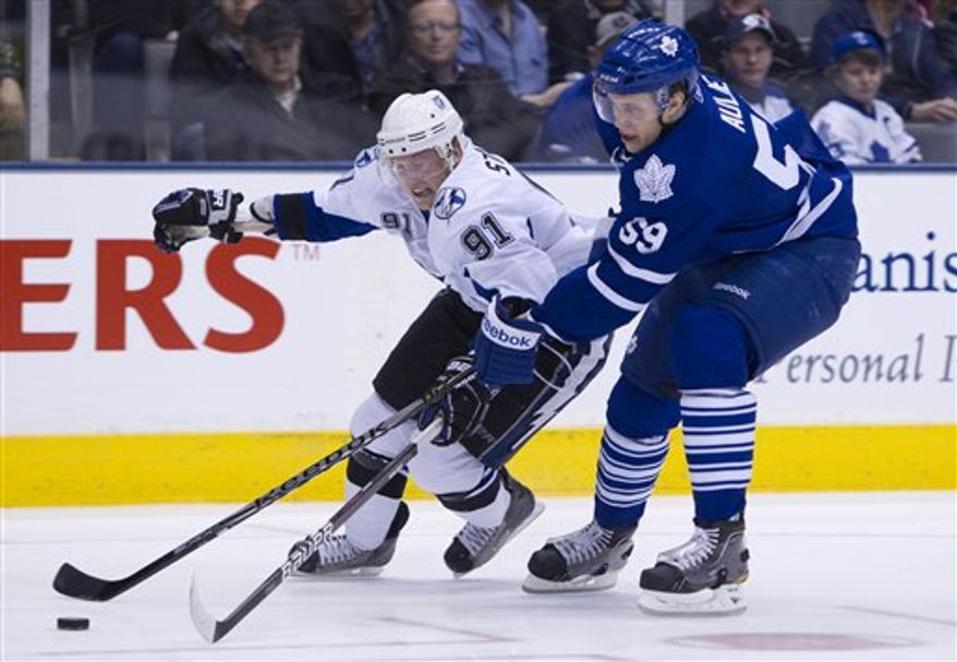 Toronto Maple Leafs' Keith Aulie, right, and Tampa Bay Lightning's Steven Stamkos battle for the puck during the first period of an NHL hockey game in Toronto on Monday, March 14, 2011. (AP Photo/The Canadian Press, Darren Calabrese