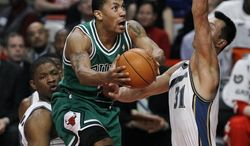 Chicago Bulls guard Derrick Rose, center, drives to the basket past the defense of Washington Wizards forward Kevin Seraphin, left, and forward Yi Jianlian, during the first half of an NBA basketball game, Tuesday, March 15, 2011, in Chicago. (AP Photo/Charles Rex Arbogast)