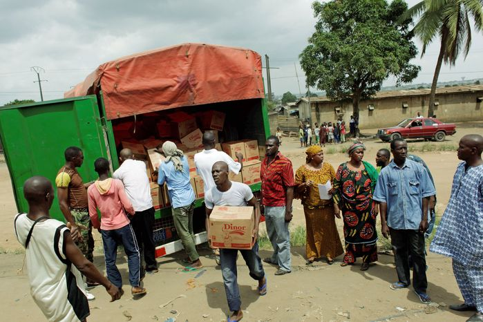 Neighborhood residents unload supplies of rice, sugar, and other staples donated by Dominique Ouattara, wife of internationally-recognized president Alassane Ouattara, in Abidjan on Saturday. Commandos have driven out attacking security forces from the pro-Ouattara area, but most businesses remain closed and a beleagured population struggles to get access to basic goods. (Associated Press)