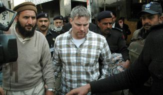 ** FILE ** Raymond Allen Davis is escorted to a court in Lahore, Pakistan, in January 2011. (Associated Press)