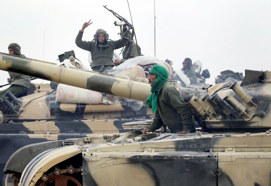 Libyan soldiers loyal to Moammar Gadhafi's regime pause at the western entrance to Ajdabiya. (Associated Press)