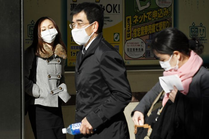 People wearing surgical masks leave Shimbashi train station in Tokyo Wednesday, March 16, 2011. The nuclear crisis has triggered international alarm and partly overshadowed the human tragedy caused by Friday's earthquake and the subsequent tsunami. (AP Photo/Eugene Hoshiko)