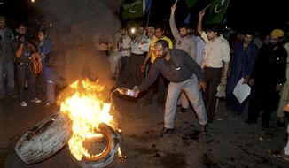 """Pakistani protesters burn tires during a demonstration against the release of Raymond Allen Davis, an American CIA contractor, on Wednesday, March 16, 2011, in Lahore, Pakistan. Mr. Davis, who said he shot and killed two Pakistani men in self-defense, was released from prison after the United States paid """"blood money"""" to the families of the victims, apparently defusing what had been a major row between Washington and Islamabad, Pakistani officials said. (AP Photo/K.M. Chaudary)"""