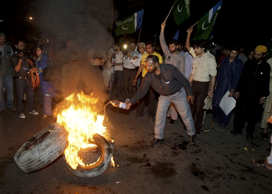 "Pakistani protesters burn tires during a demonstration against the release of Raymond Allen Davis, an American CIA contractor, on Wednesday, March 16, 2011, in Lahore, Pakistan. Mr. Davis, who said he shot and killed two Pakistani men in self-defense, was released from prison after the United States paid ""blood money"" to the families of the victims, apparently defusing what had been a major row between Washington and Islamabad, Pakistani officials said. (AP Photo/K.M. Chaudary)"