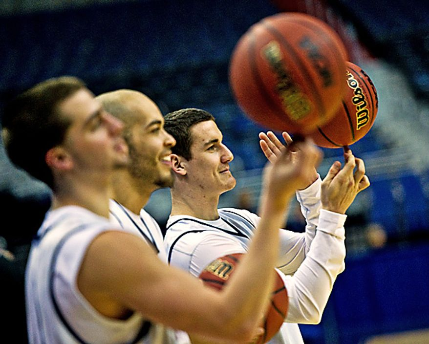 Far right, University of Connecticut player P.J. Cochrane spins the ball during open practice at the Verizon Center, in Washington, Wednesday, March 16, 2011. (Drew Angerer/The Washington Times)