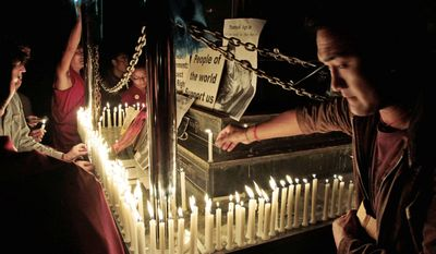 Exiled Tibetans light candles to honor the monk who set himself on fire in protest against China's government. (Associated Press)