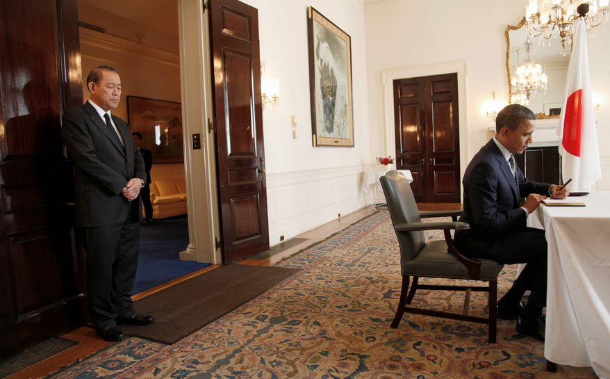 President Obama signs the condolence book as Ichiro Fujisaki, the Japanese ambassador to the U.S., looks on during his visit to the Japanese Embassy in Washington on Thursday. Mr. Obama placed a telephone call to Prime Minister Naoto Kan on Wednesday to discuss Japan's efforts to recover from last week's devastating earthquake and tsunami, and the nuclear crisis at the Fukushima Dai-chi plant. (Associated Press)