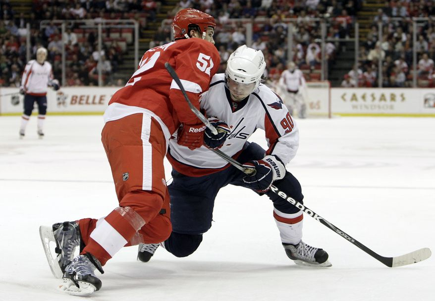 Detroit Red Wings defenseman Jonathan Ericsson (52), of Sweden, holds up Washington Capitals center Marcus Johansson (90), of Sweden, in the second period of an NHL hockey game in Detroit, Wednesday, March 16, 2011. Ericsson was called for interference on the play. (AP Photo)