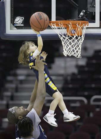 Marquette's Chris Otule lifts Mason, the daughter of Marquette head coach buzz Williams, to shoot the final basket of practice in the second round of the East Region in the NCAA college basketball tournament in Cleveland on Thursday, March 17, 2011.  Marquette will face Xavier on Friday. (AP Photo/Amy Sancetta)