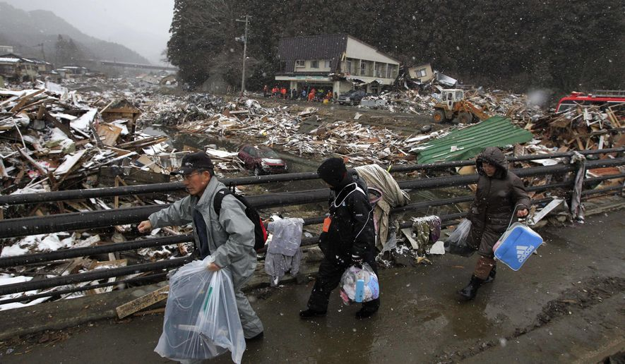 Residents of Kamaishi, Japan, walk away with personal items that they recovered from their damaged home in the aftermath of Friday's tsunami. Two search-and-rescue teams from the United States and one from the United Kingdom with a total of about 220 personnel searched the town for survivors on Thursday, March 17, 2011. (AP Photo/Matt Dunham)
