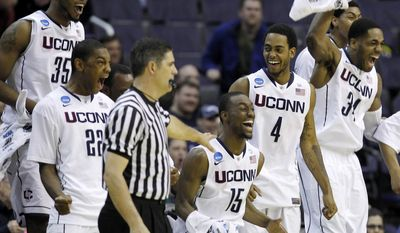 Connecticut players, from left, center Charles Okwandu, forward Roscoe Smith, guard Kemba Walker, forward Jamal Coombs-McDaniel and center Alex Oriakhi celebrate on the bench during the second half of the West regional second round NCAA tournament college basketball game against Bucknell, Thursday, March 17, 2011, at the Verizon Center in Washington. Connecticut defeated Bucknell 81-52. (AP Photo)